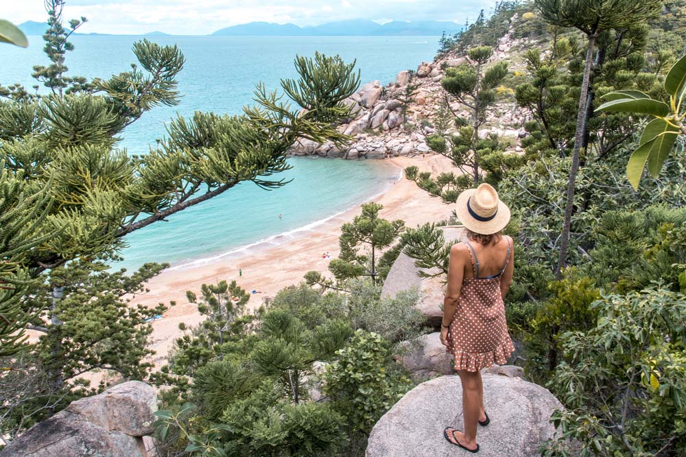 a girl in a dress standing on a rock surrounded by trees; she enjoys the view on Arthur Bay on Magnetic Island