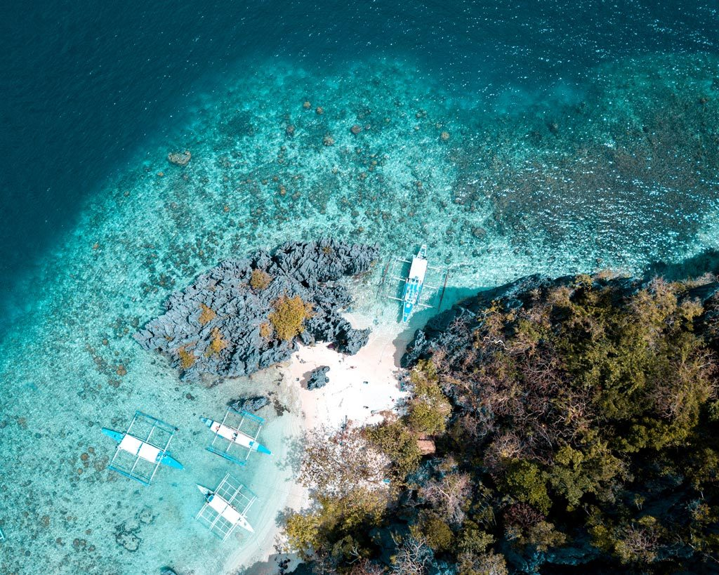 drone view on blue wate, boats and island in the Philippines