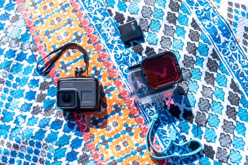 A gopro and gopro accessories spread out on a blanket