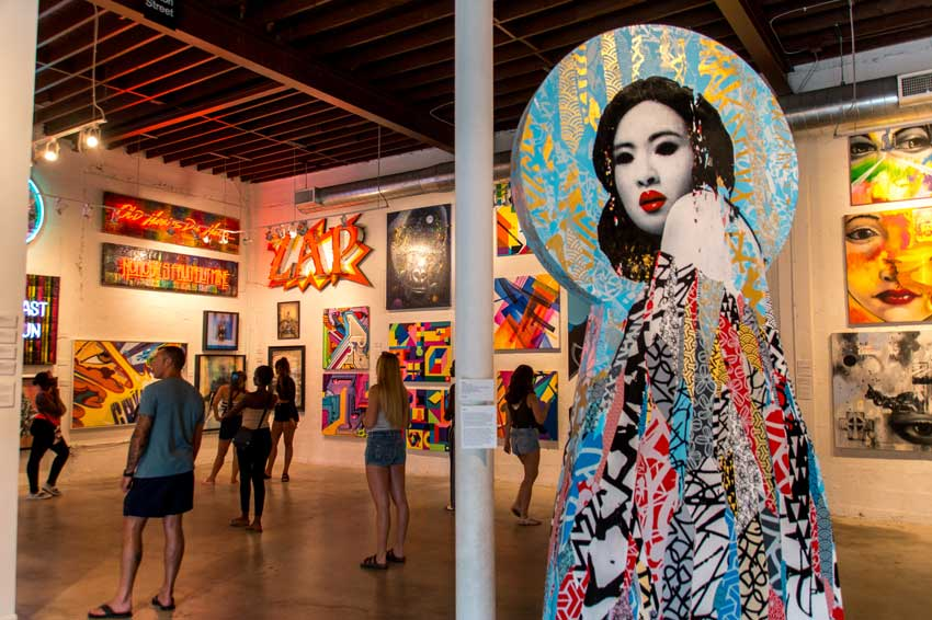 Wynwood gallery with colourful pictures and many people standing