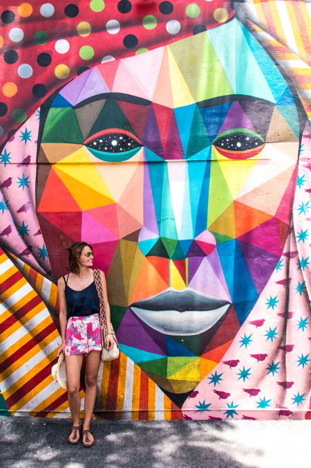 a woman standing in front of the colourful face and thinking how to plan a perfect travel itinerary