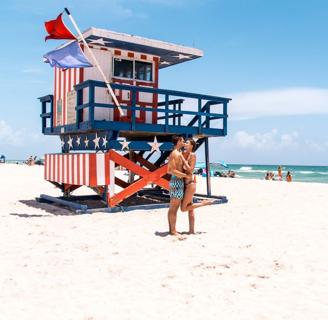 taking photo with american lifeguard hut with two individuals in front of it, one of the best things to do in Miami