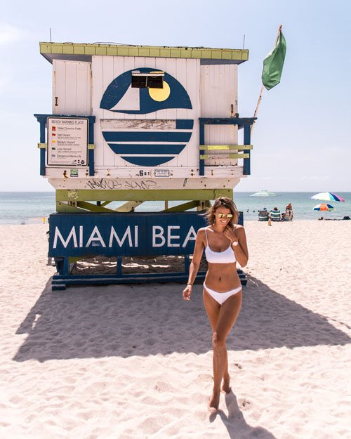 a girl posing in front of the iconic Miami beach sign hut, one of the coolest thing to do in Miami
