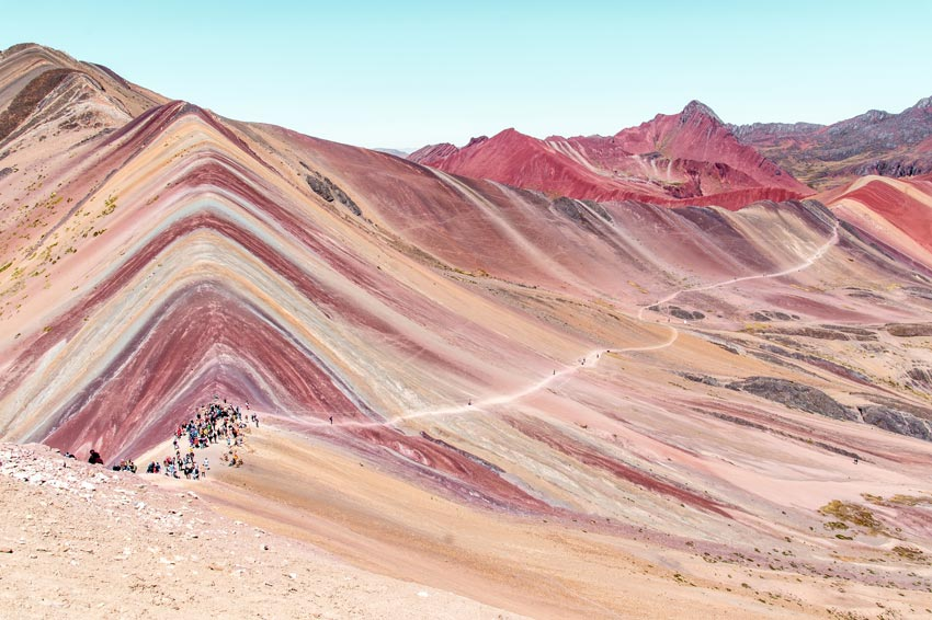 a red mountain with people in the background and the path to the Red Valley