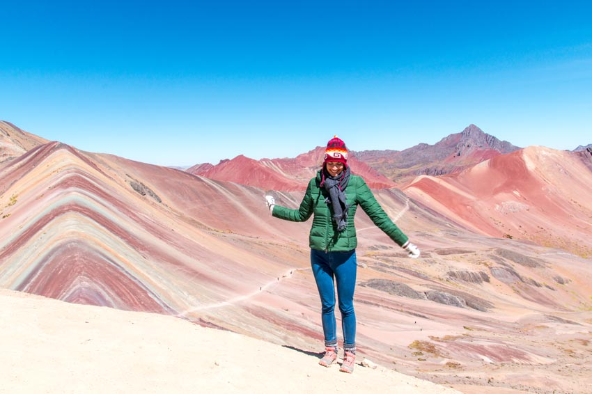a girl jumping on the top of the Colourful Mountain in Peru
