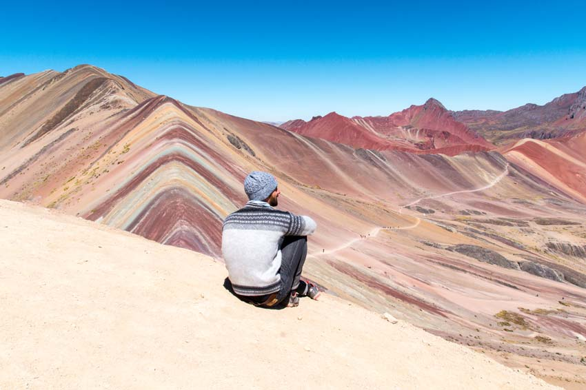 a man sitting and enjoying the view on colourful mountains and Red Valley