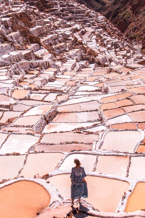 a girl standing in front of pink salt pools with fantastic view Salinas