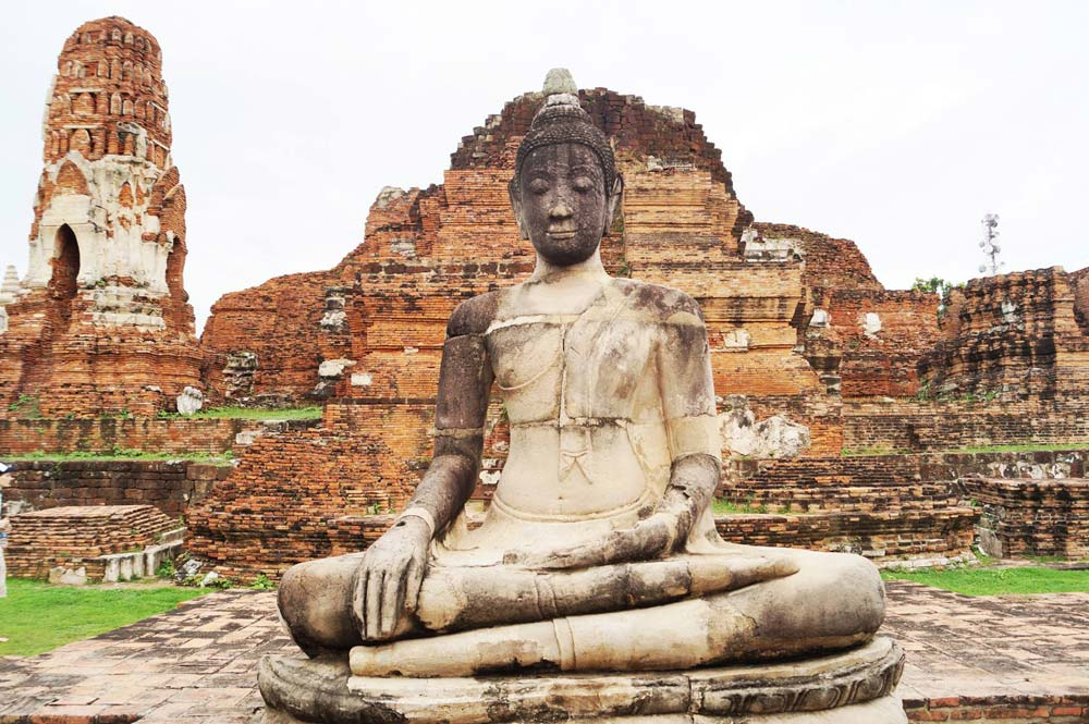 a buddha statue in front of old temple buildings