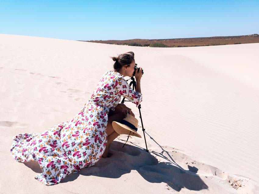 a brunette holding a camera attached to a tripod in white sand dunes
