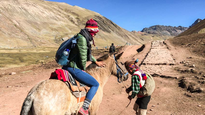 a girl getting on a horse to Montana de Siete Colores