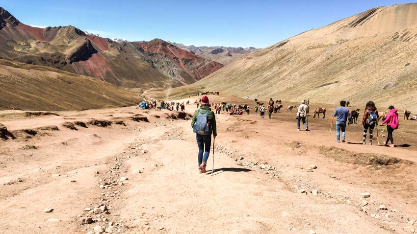 a woman and several other people hiking down a path into a valley