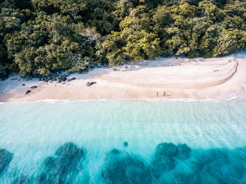 Aerial view on a couple walking down Nude Beach on Fitzroy Island in Queensland