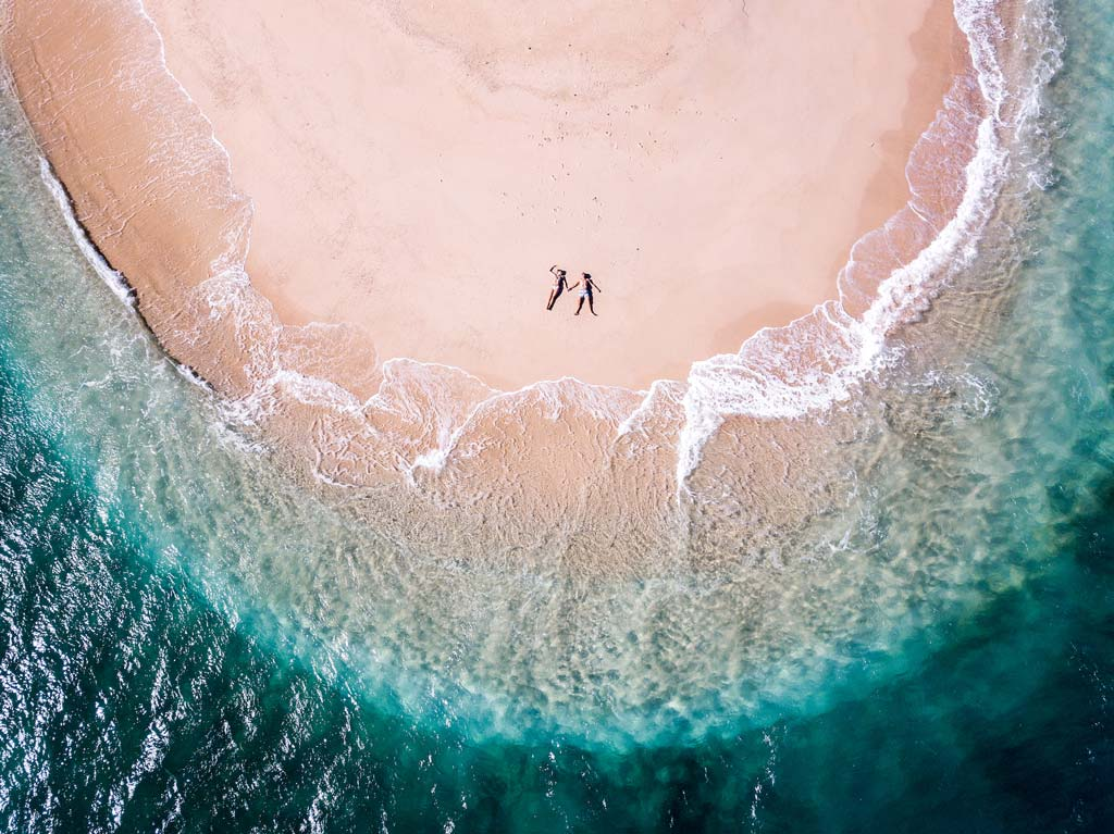 aerial view on a couple lying on a beach surrounded by water with different shades of blue