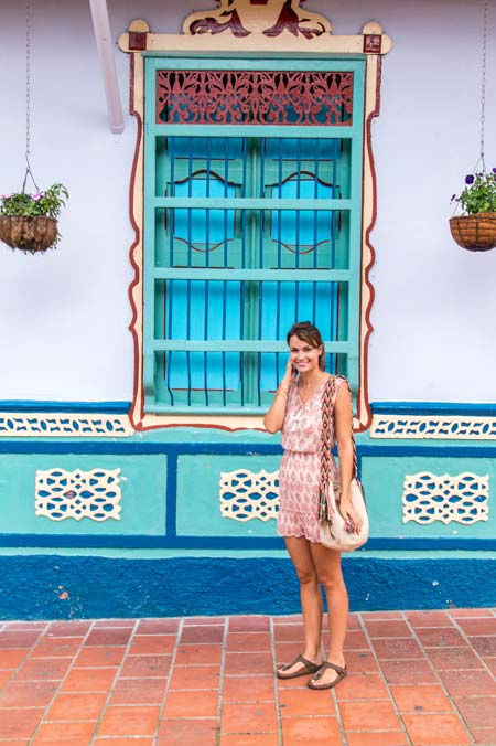 a lady posing in front of a colorful house with several paintings