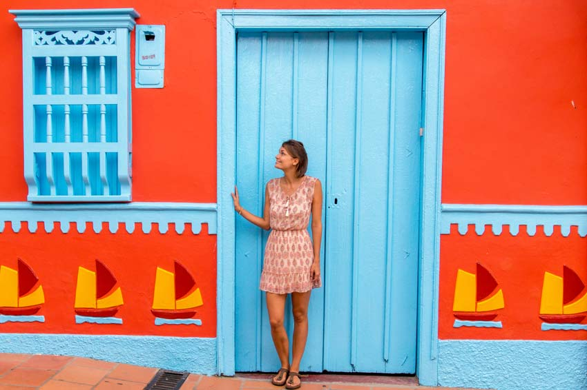 a lady standing in front of blue door in Guatape nearby Medellin