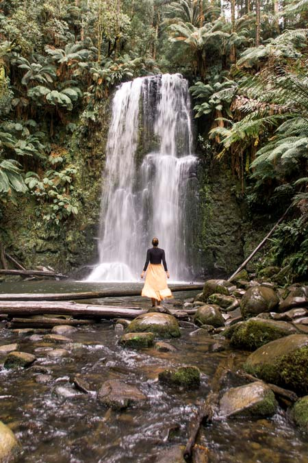 a woman standing in front of a waterfall surrounded by lush jungle