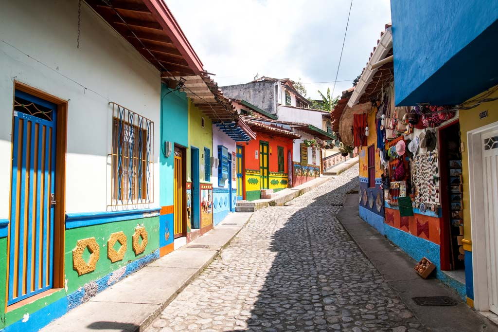 view into a cobblestone street with colorful painted houses in Guatape