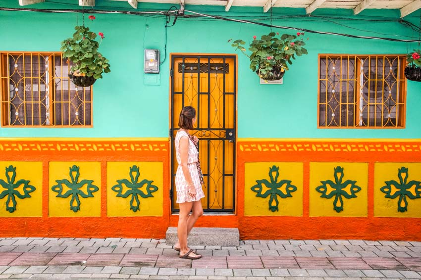 A woman walking on cobblestones in front of a colorful painted house in Guatape Medellin