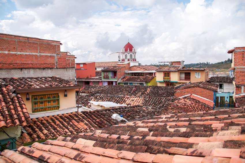 the view on rooftops with a church tower in the distance