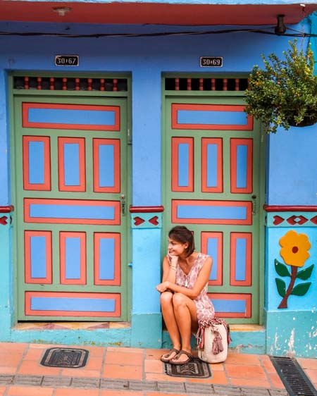 a lady sitting in front of a colorful door