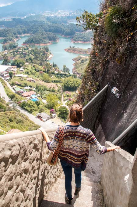 a woman walking down a steep staircase with a view on a lake, houses and trees