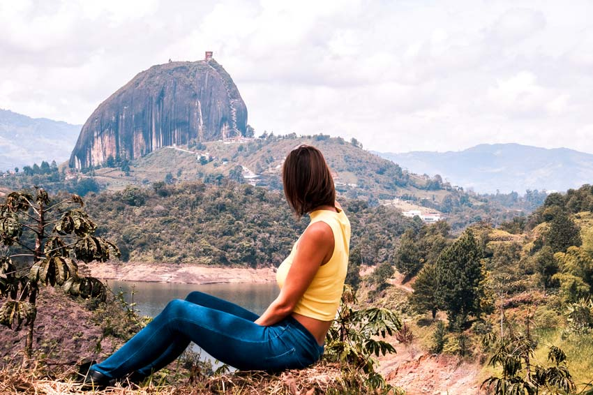 woman sitting on the ground facing towards a big rock called piedra del penol in the distance