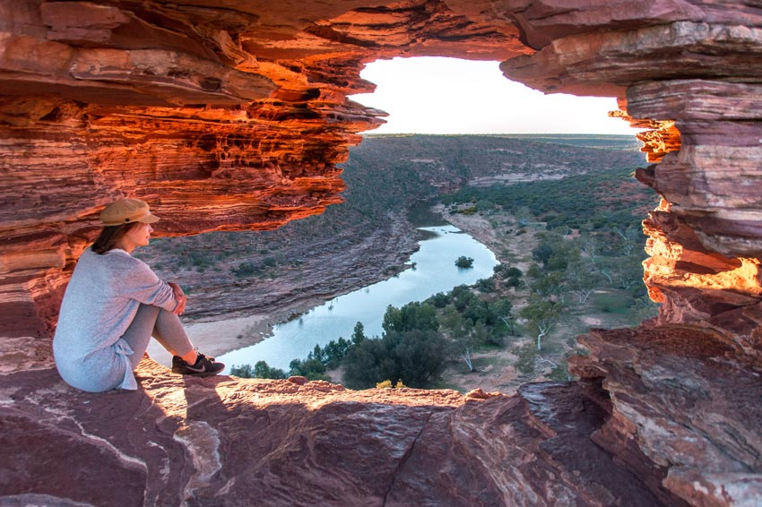 a woman sitting inside a rockhole looking out over a wide gorge with a river at the bottom of it