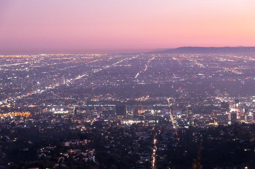 a view during sunset on Los Angeles, pink sky and city lights