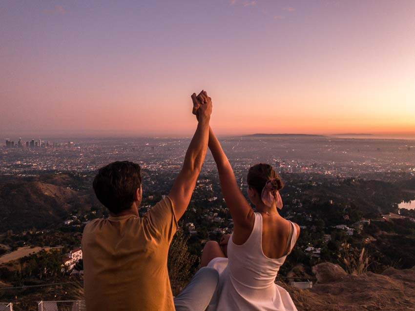 Two people holding hands with a view on Los Angeles during sunset