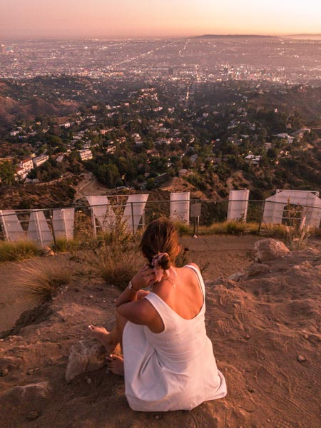 a girl in a white dress sitting on the ground behind the Hollywood sign during the sunset hour