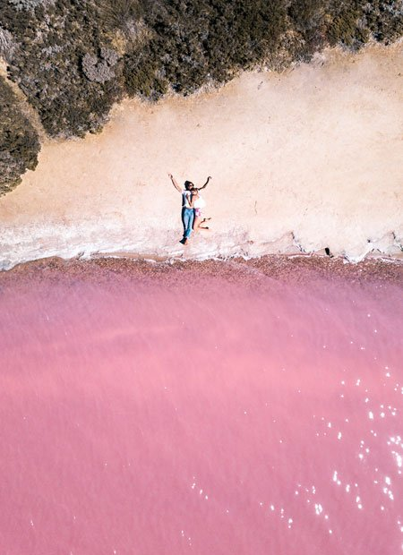2 people lying on the shore and the view on pink water and green bush