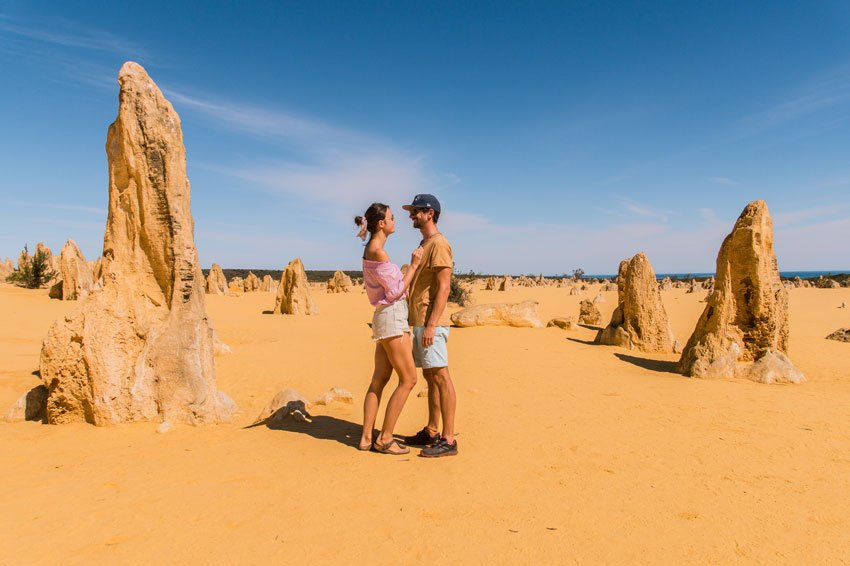 a couple looking at each other besides several rock formations in the pinnacle dessert one of the most famous place in Australia