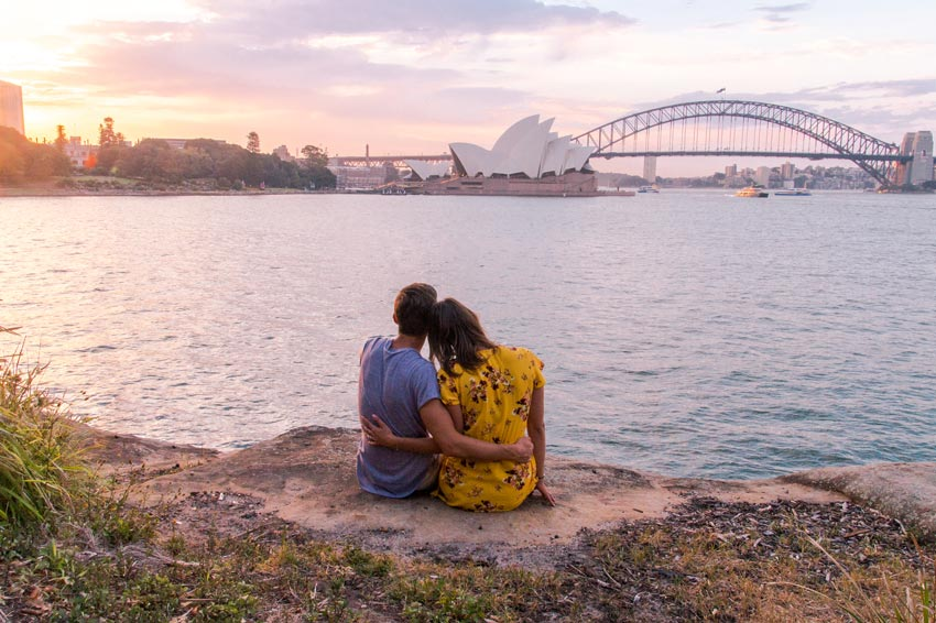 a couple sitting next to each other and enjoying the view on the australian landmark Sydney Opera House during sunset