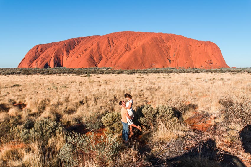a man lifting up a woman in front of Uluru one of the most beautiful landmarks in Australia
