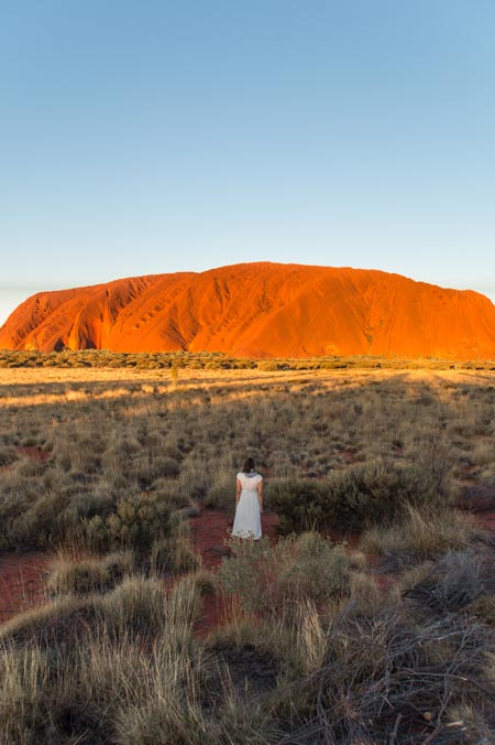 Woman standing in the middle with a view on the red rock, called Uluru, one of the most iconic landmarks in Australia