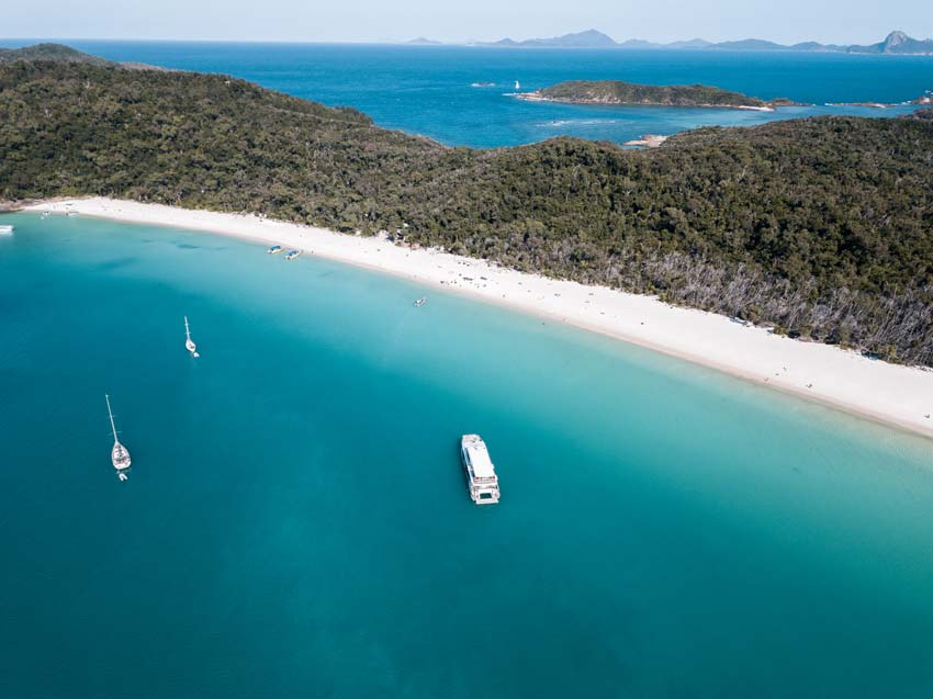aerial view on whitehaven beach with several boats in the water
