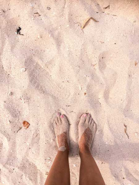 view on feet standing on pink sand beach in Labuan Bajo, Indonesia