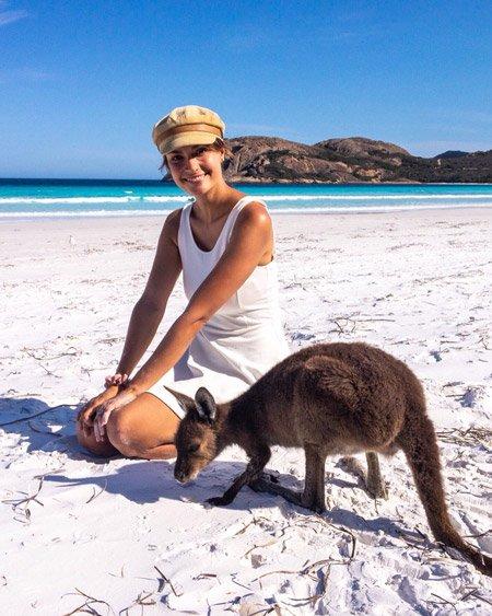 a woman sitting next to a kangaroo on a beach