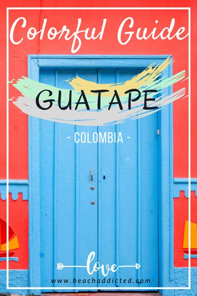 red wall and blue door with a sign: Guatape, Colombia