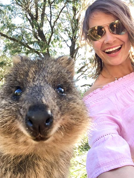 A woman wearing a pink top is taking a selfie with quokka