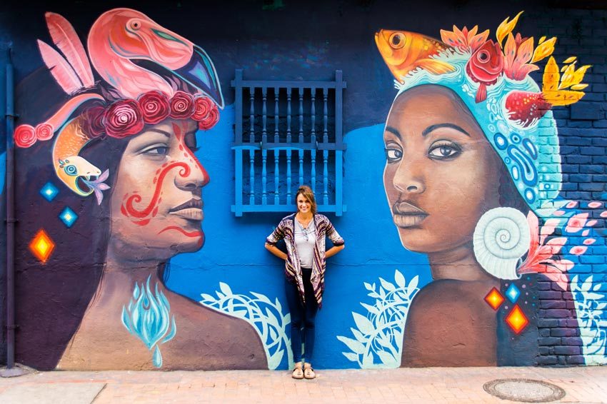 a pretty girl posing in front of a mural displaying men and woman in Bogota, Colombia