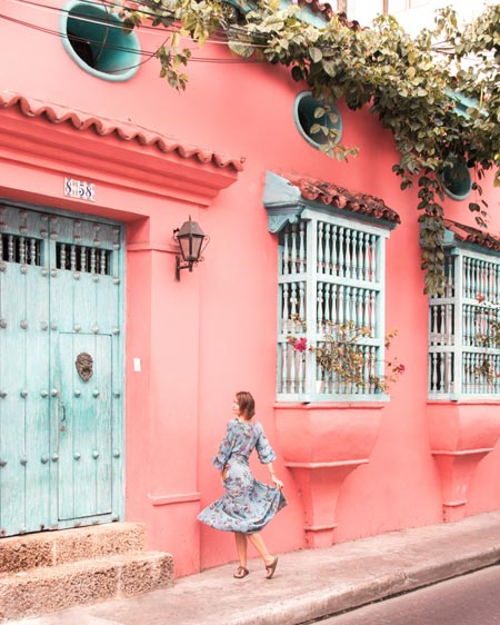 woman in front of pink wall in Cartagena which has to be in your 2 weeks itinerary when visiting Colombia