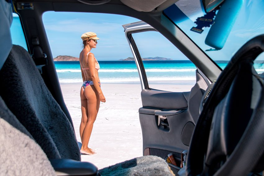 A picture framed by the inside of a car showing a girl standing on a beach with the ocean in the background