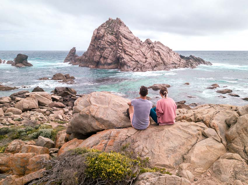 two people sitting on the rock, with rocks and ocean in the background, awesome stop on the way from Perth to Esperance.