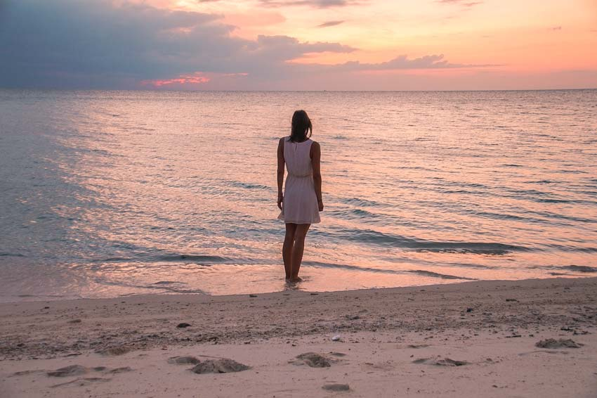 a woman standing on the beach with a pink sunset colours and the ocean