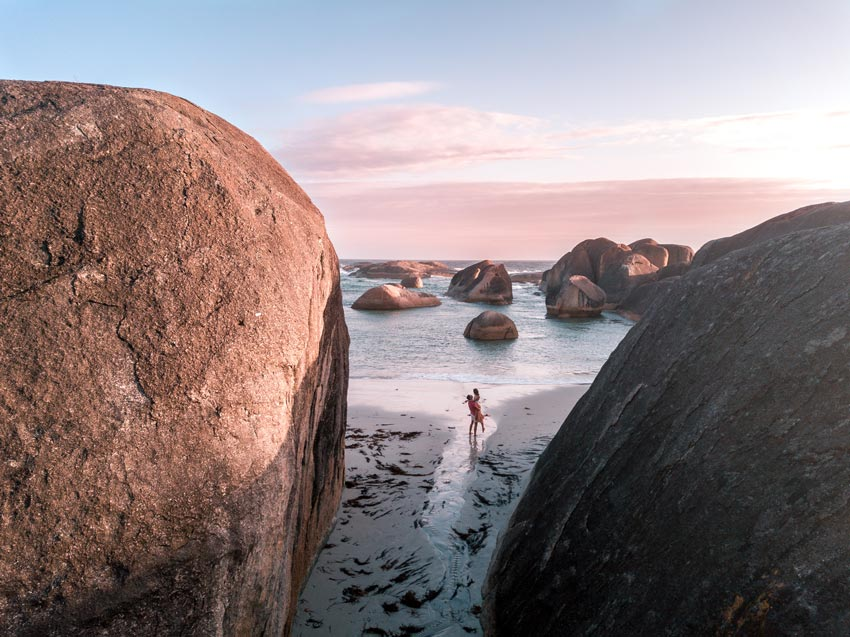 arial shot with two people standing on the beach between two big rocks and pink sky in the background
