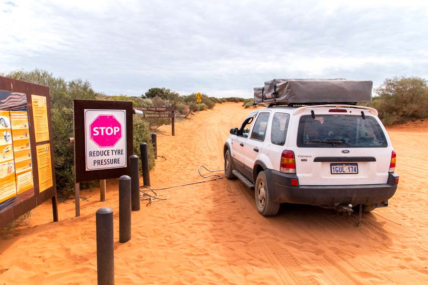 a white car standing on the  orange sand with a sign: Stop and reduce tyre pressure.
