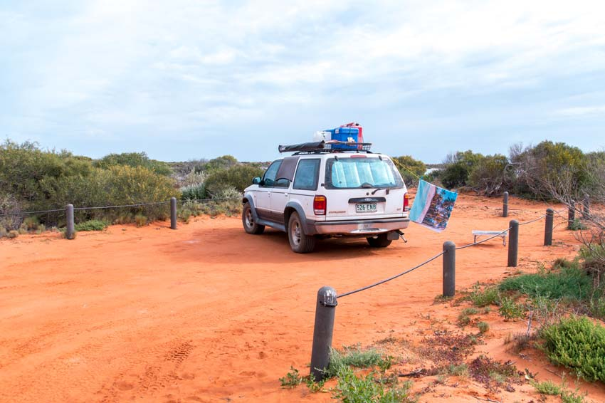 a 4WD car standing on the red sand with green bush around
