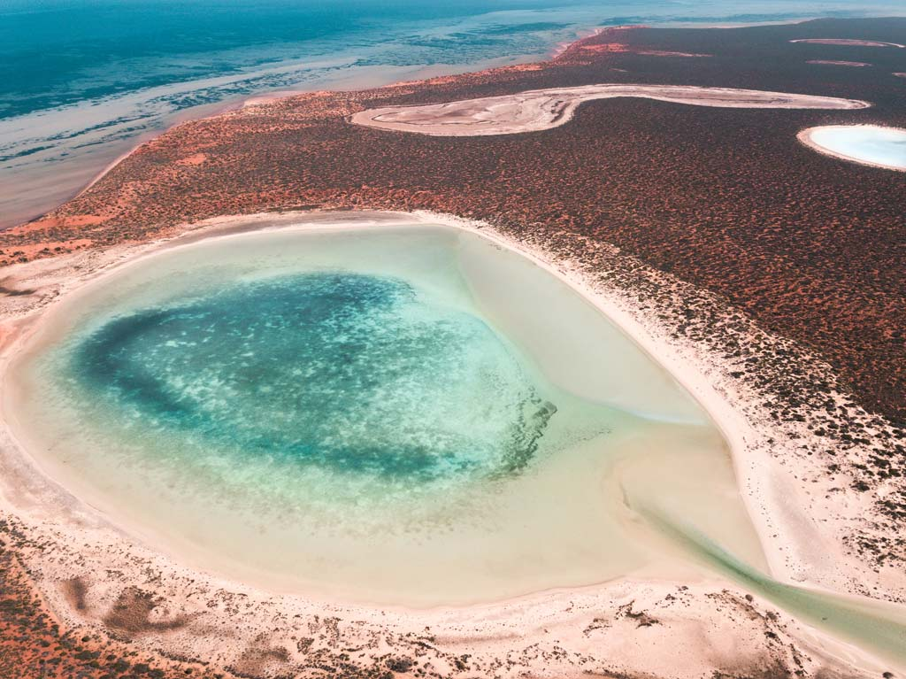 an aerial view on blue lagoons, red sand, part of Francios National Park which is one of the best things to do in Shark Bay