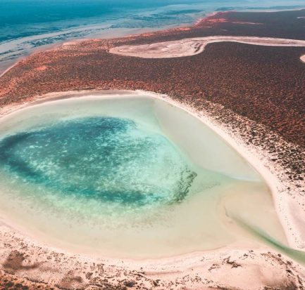 an arial view on lagoon with blue water and red sand in Shark Bay